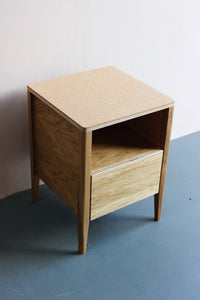 Handmade bedside table. It features cork top, oak veneered ply and solid oak legs. Made by Jon Grant London in Leyton, East London.