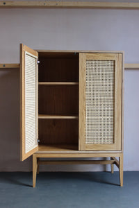 Mid-century style rattan cane cabinet featuring oak veneered plywood, solid oak legs and woven cane in-lay. Designed and made by Jon Grant London in Leyton, East London.