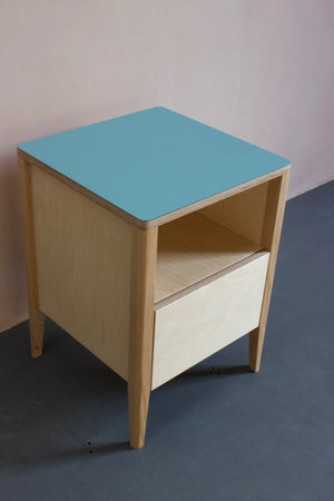 Handmade bedside table, perfect for a modern home. It features Forbo lino top with plywood carcass and solid ash legs. Made by Jon Grant London in Leyton, East London.