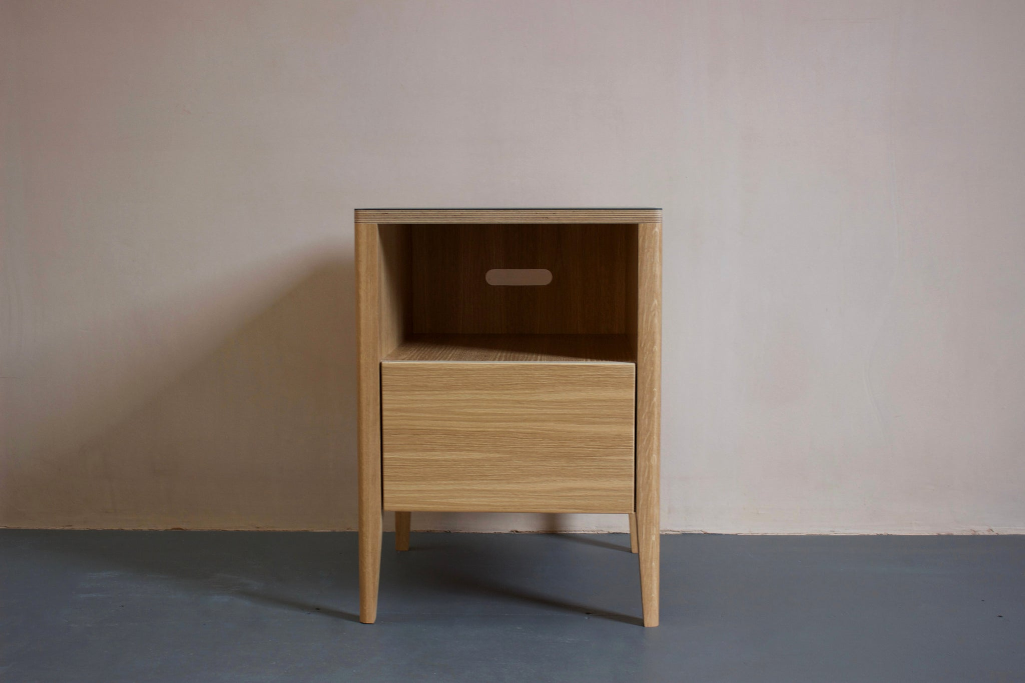 The Huxley bedside table in oak veneer plywood with Forbo linoleum top and solid oak legs. Designed and made by Jon Grant London in Leyton, East London.