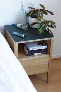 Handmade contemporary bedside table, perfect for a modern home. It features Forbo linoleum top with oak veneered plywood and solid oak legs. Designed and made by Jon Grant London in Leyton, East London.