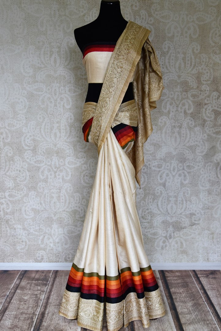 Shop cream tussar silk sari online in USA with striped and embroidered border. Make your style extraordinary on weddings and special occasions with Indian designer sarees, traditional silk sarees, embroidered sarees from Pure Elegance Indian clothing store in USA.-full view