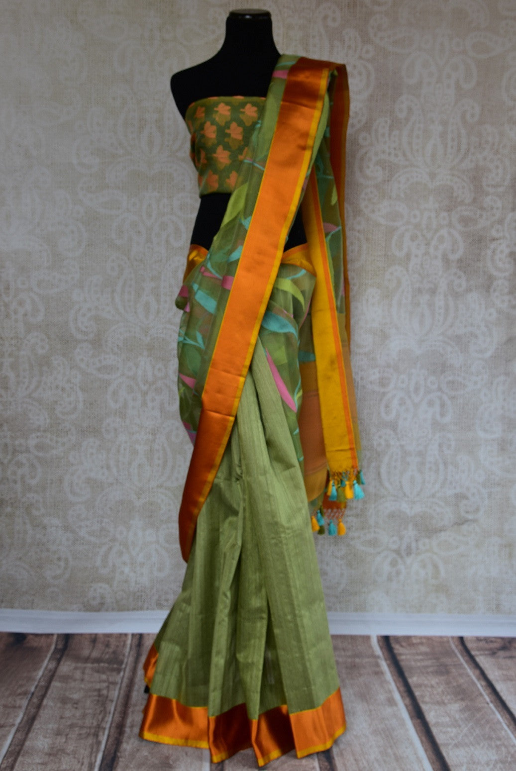 90C107 Half matka, half organza, kota satin Banarasi saree. The green floral saree with orange-gold border, available online at our ethnic wear store in USA, is ideal for ethnic festivities