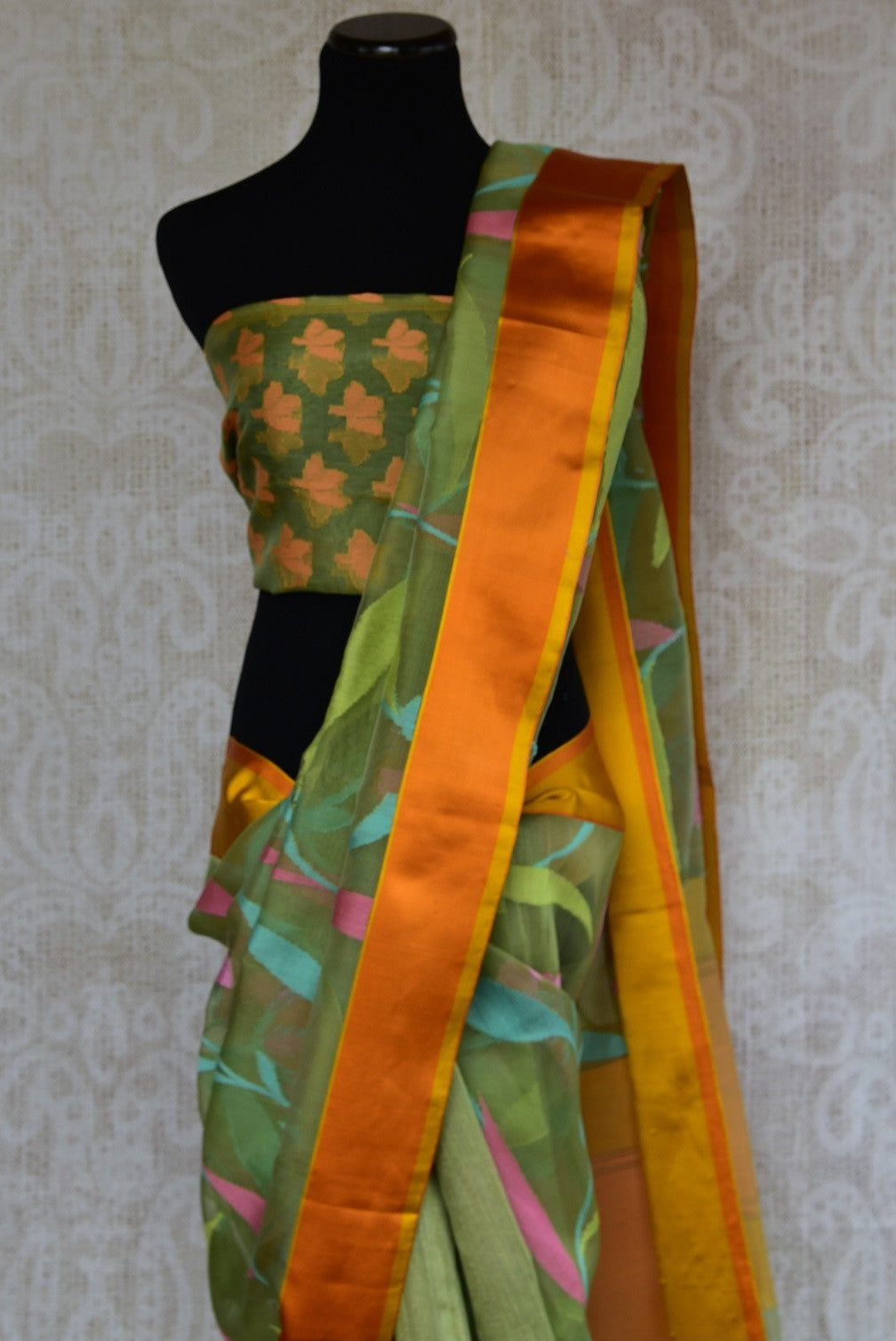 90C107 Half matka, half organza, kota satin Banarasi saree. The green floral saree with orange-gold border, available at our Indian clothing store online in USA, is ideal for ethnic festivities
