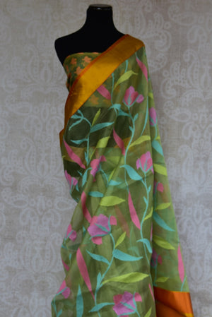 90C107 Half matka, half organza, kota satin Banarasi saree. The floral saree comes in a beautiful shade of green and is topped with orange-gold border. Buy it online at our store in USA, is ideal for ethnic festivities