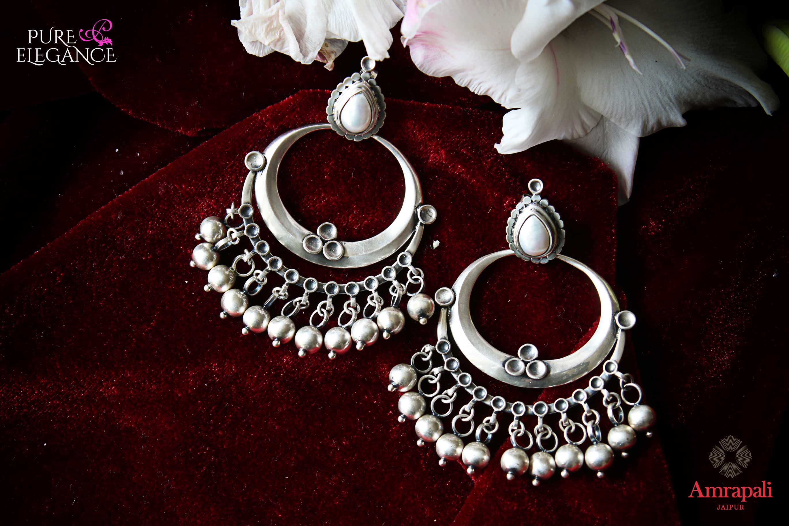 Shop Amrapali silver chandbali earrings with pearl drops online in USA. Find an exquisite collection of handcrafted Indian jewelry in USA at Pure Elegance Indian fashion store. Complete your festive look with beautiful silver gold plated necklaces, silver gold plated earrings, silver jewelry from our online store.-flatlay