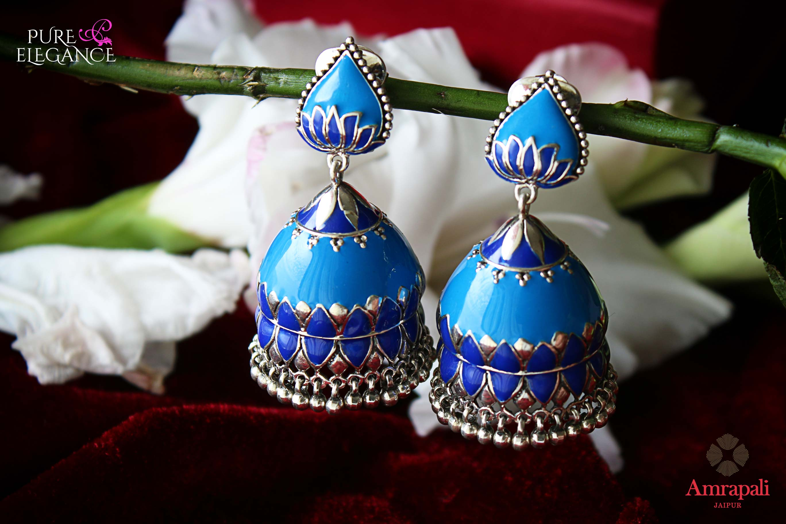 Shop Amrapali silver blue enamel jhumka earrings online in USA. Find an exquisite collection of handcrafted Indian jewelry in USA at Pure Elegance Indian fashion store. Complete your festive look with beautiful silver gold plated necklaces, silver gold plated earrings, silver jewelry from our online store.-flatlay