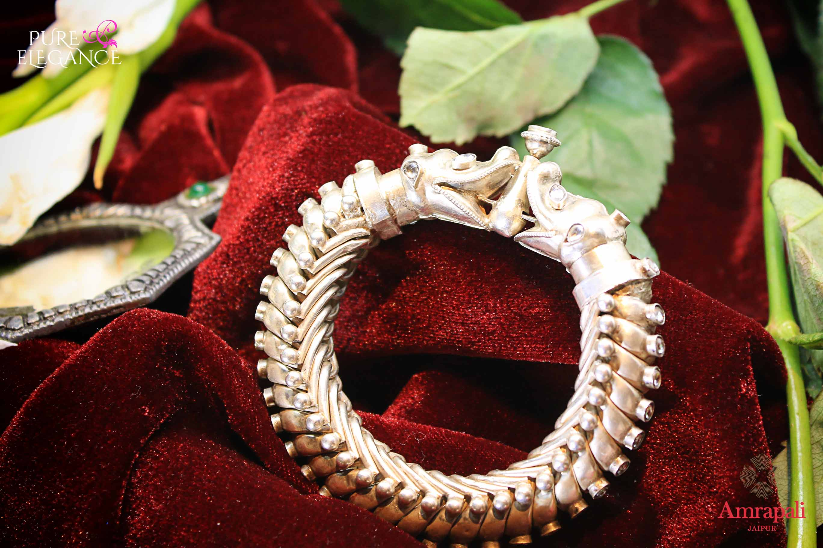 Buy Amrapali white glass studded heavy silver bangle online in USA. Find an exquisite collection of handcrafted silver gold plated jewelry in USA at Pure Elegance Indian fashion store. Complete your festive look with traditional Indian jewelry, silver gold plated earrings, silver jewellery from our online store.-flatlay