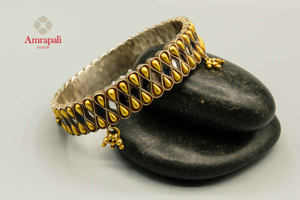 Shop Amrapali silver gold plated two-tone drop design bangle online in USA. Raise your traditional fashion quotient on special occasions with exquisite Indian jewelry from Pure Elegance Indian clothing store in USA. Enhance your look with silver gold plated jewelry, fashion jewelry available online.-flatlay