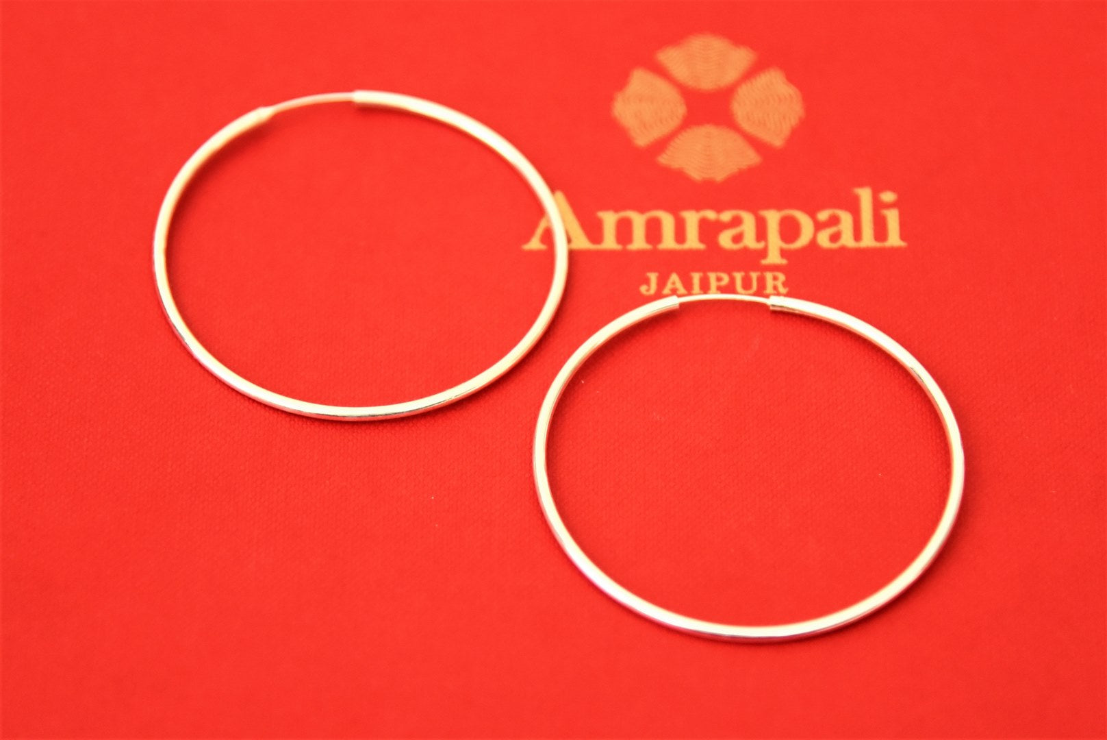 Buy Amrapali classic silver hoop earrings online in USA. Choose from a beautiful range of Indian jewelry, silver jewelry, silver earrings, gold plated jewelry from Pure Elegance Indian fashion store in USA.-flatlay