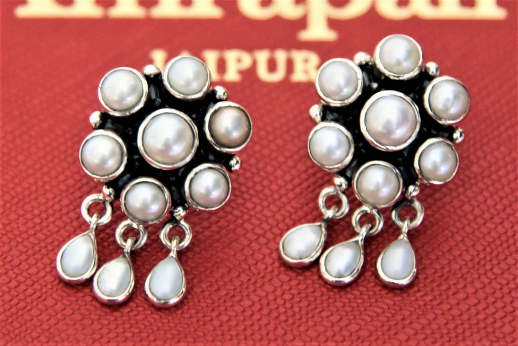 Shop Amrapali silver floral pearl stud earrings online in USA. Give yourself a beautiful traditional makeover this wedding season with exquisite gold plated jewellery, silver jewelry from Pure Elegance Indian fashion boutique in USA.-flatlay