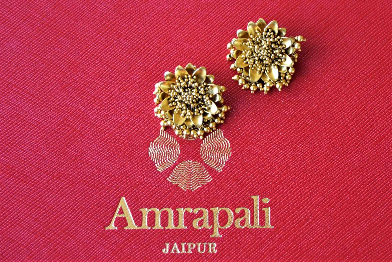 Buy Amrapali silver gold plated flower stud earrings online in USA with golden beads. Elevate your ethnic attires with exquisite Indian jewelry, silver earrings, silver gold plated necklaces from Pure Elegance Indian fashion store in USA.-flatlay