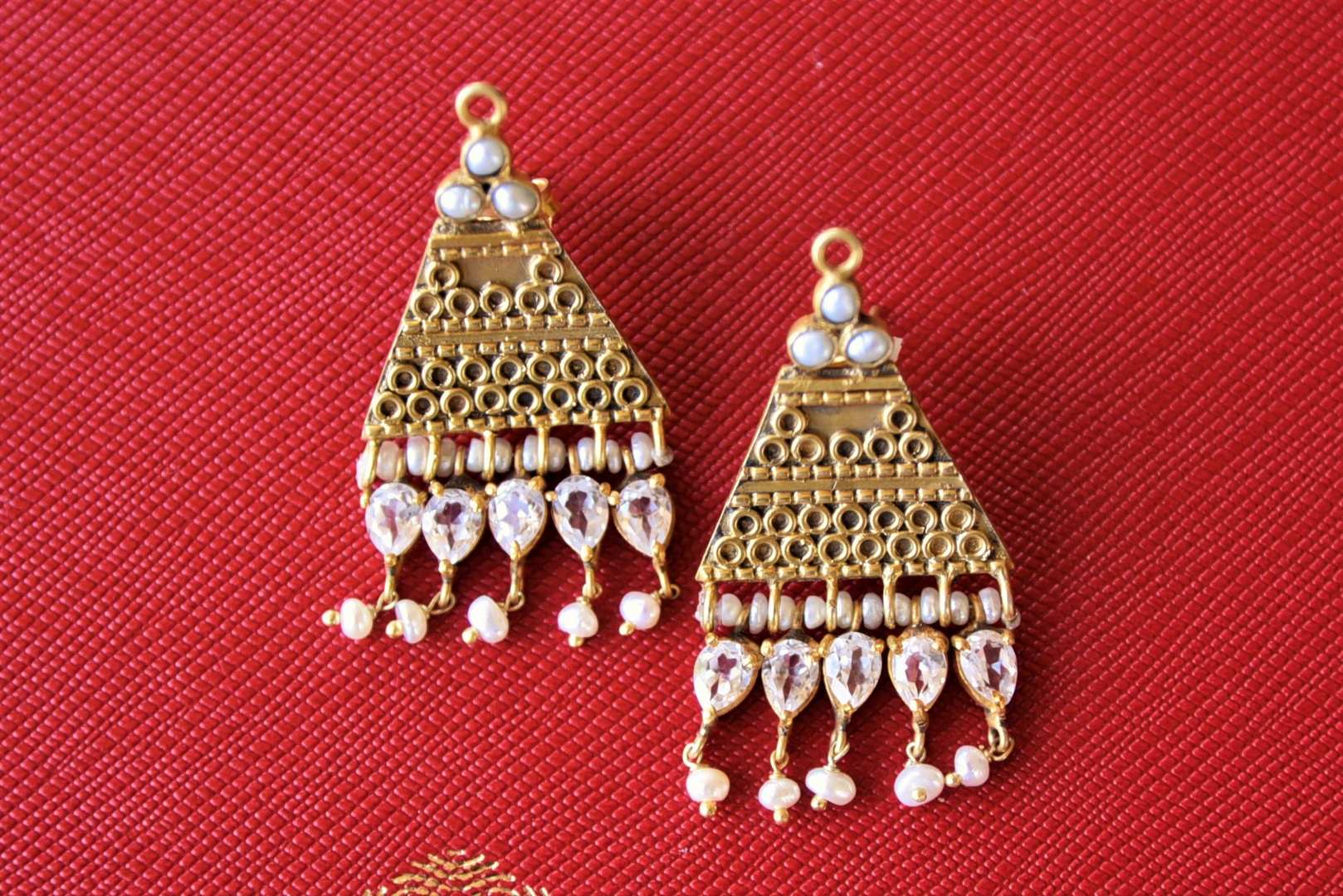 Buy Amrapali silver gold plated triangle earrings online in USA with white crystal drops. Elevate your ethnic attires with exquisite Indian jewelry, silver gold plated earrings, silver gold plated necklaces from Pure Elegance Indian fashion store in USA.-flatlay