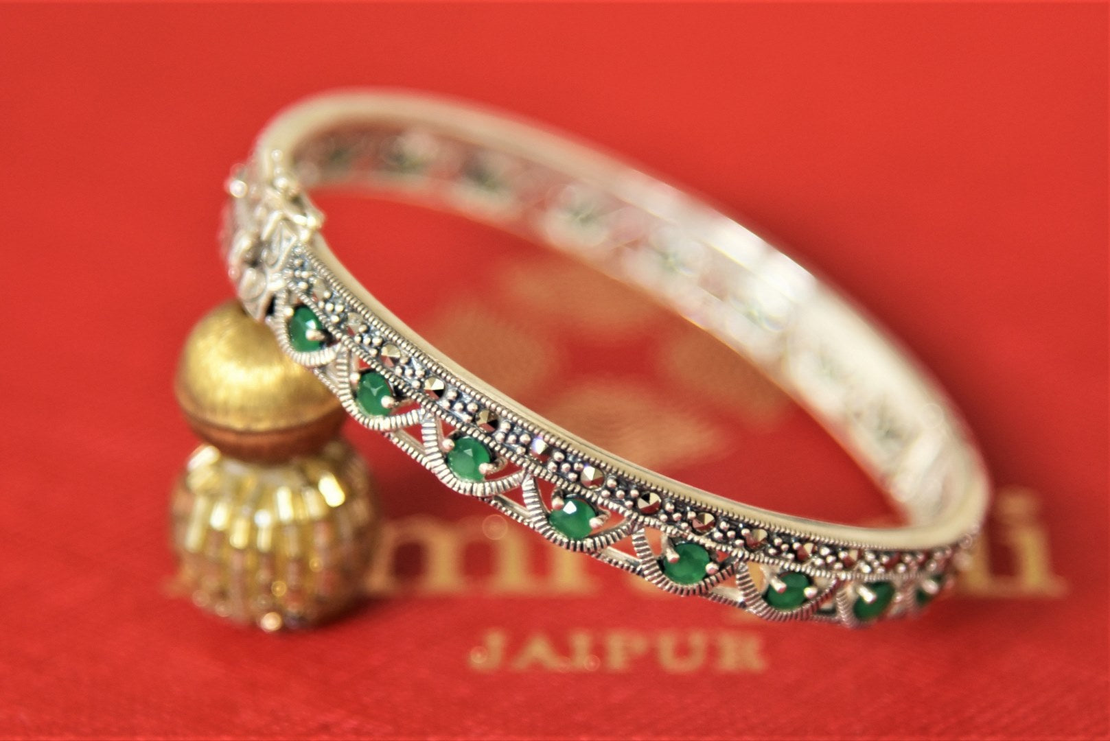 Shop Amrapali green stones silver bangle online in USA. Give yourself a beautiful traditional makeover this wedding season with exquisite gold plated jewellery, silver jewelry from Pure Elegance Indian fashion boutique in USA.-flatlay