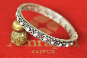 Buy Amrapali pearl silver bangle online in USA. Give yourself a beautiful traditional makeover this wedding season with exquisite gold plated jewellery, silver jewelry from Pure Elegance Indian fashion boutique in USA.-flatlay