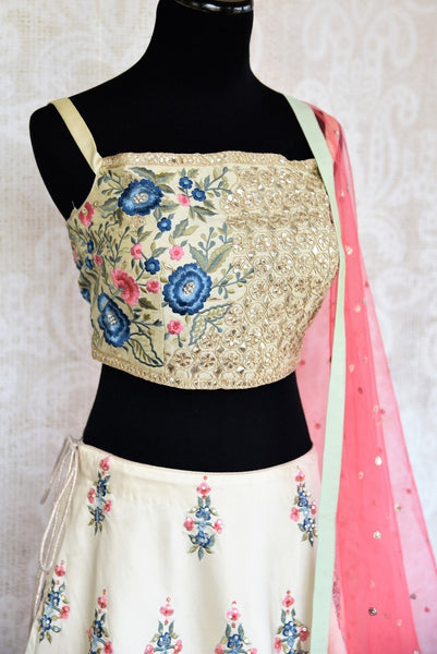 Buy beautiful off-white embroidered lehenga choli set online in USA. The elegant attire is a perfect pick for an Indo-western look at wedding and parties. Get floored by an exclusive collection of Indian designer lehengas in USA available at Pure Elegance fashion store or shop online.-side view