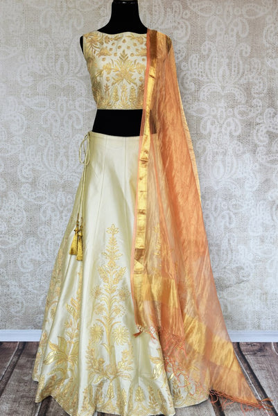 Buy beautiful cream embroidered silk lehenga choli set online in USA. The elegant attire is a perfect pick for an ethnic look at wedding and parties. Get floored by an exclusive collection of Indian designer lehengas in USA available at Pure Elegance fashion store or shop online.-full view