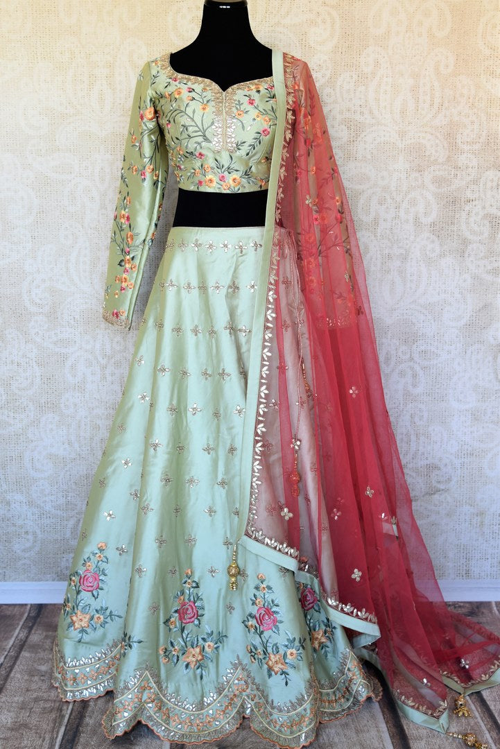 Buy pista green embroidered silk lehenga online in USA with pink dupatta. The lehenga is perfect for rich Indian ethnic look at weddings. Make your Indian clothing collection exquisite with beautiful Indian designer lehengas available at Pure Elegance clothing store in USA or shop online.-full view