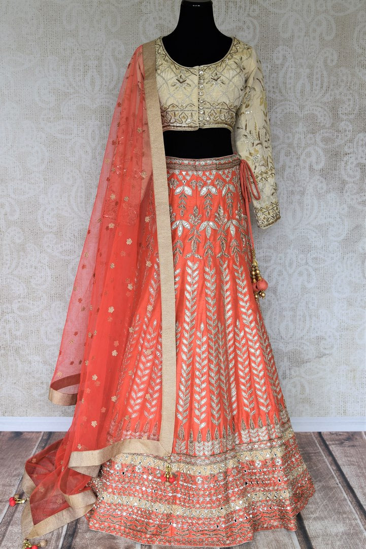 Shop the beautiful feminine coral raw silk embroidery lehenga with a cream silk embroidered blouse and peach sheer net dupatta to weddings. The authentically handcrafted silk lehenga will instantly glorify your look. Shop Indian dress online, designer lehenga online or visit Pure Elegance store in USA. -full view