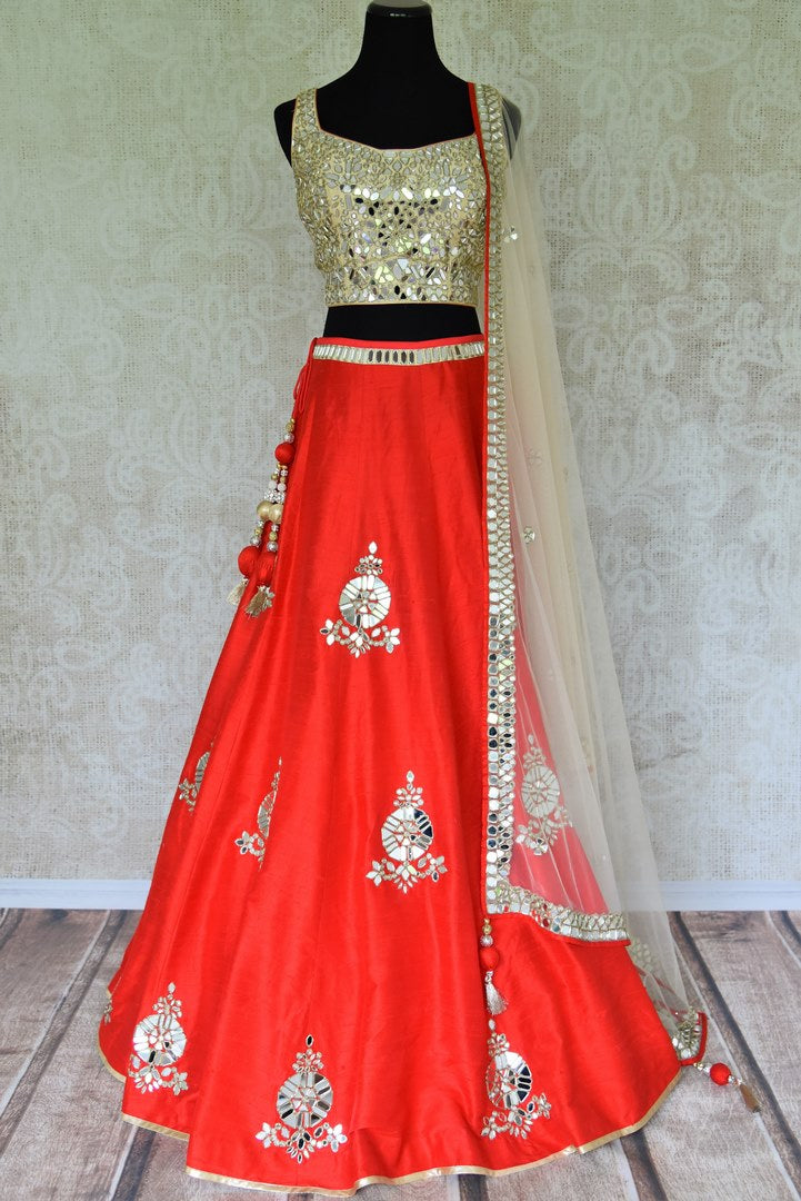 This festive season, twirl in this deep red silk mirror work lehenga complemented with a stunning mirror work blouse. The scintillating ensemble comes with a dreamy beige net dupatta with mirror work details on its borders. Shop wedding lehengas, wedding sarees, bridal dresses online or visit Pure Elegance store, USA. -full view