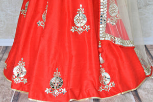 This festive season, twirl in this deep red silk mirror work lehenga complemented with a stunning mirror work blouse. The scintillating ensemble comes with a dreamy beige net dupatta with mirror work details on its borders. Shop wedding lehengas, wedding sarees, bridal dresses online or visit Pure Elegance store, USA. -lehenga