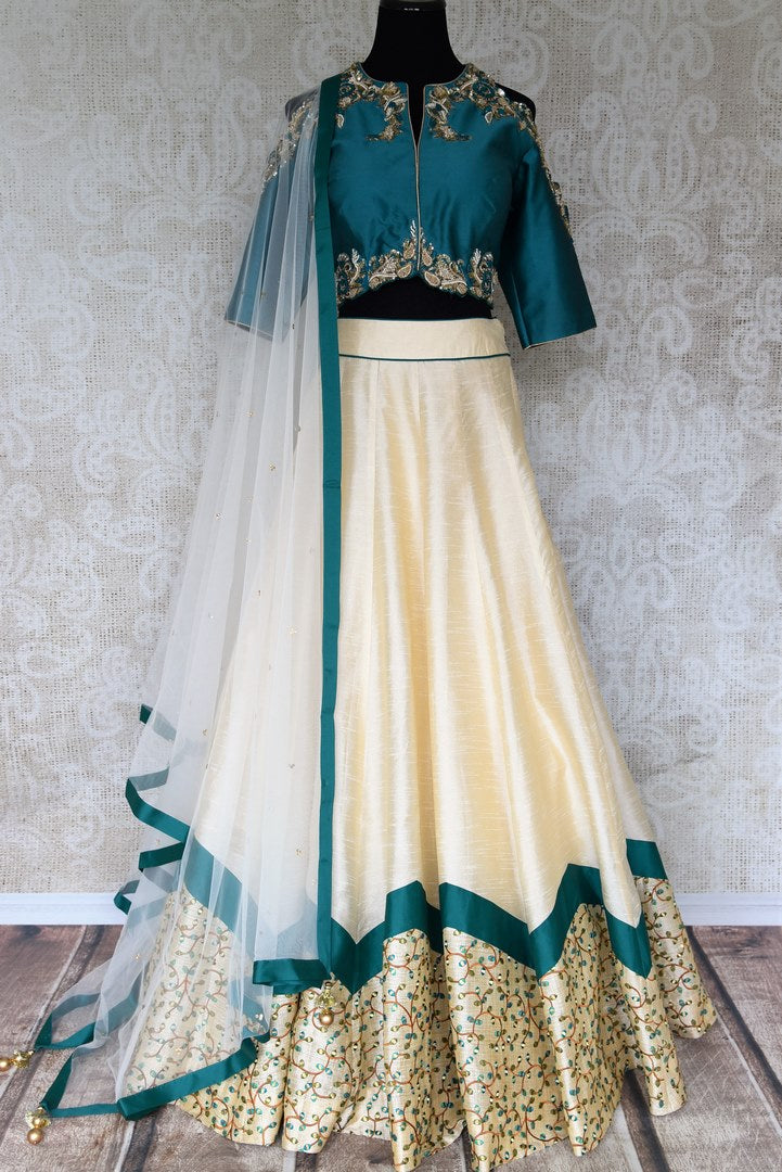 Splurge on this designer cream silk net embroidery lehenga with cream-coloured dupatta to look nothing less than a dream. Escalate your style appeal with the emerald-hued blouse embroidered to perfection and drape the dupatta. Shop beautifully handcrafted lehengas online or visit Pure Elegance store in USA. -full view