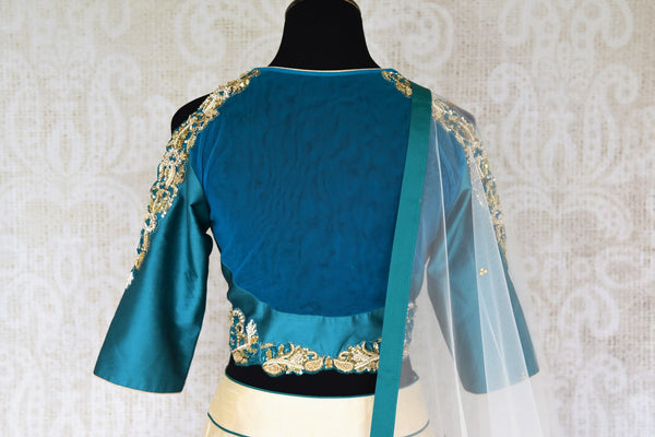 Splurge on this designer cream silk net embroidery lehenga with cream-coloured dupatta to look nothing less than a dream. Escalate your style appeal with the emerald-hued blouse embroidered to perfection and drape the dupatta. Shop beautifully handcrafted lehengas online or visit Pure Elegance store in USA. -blouse back
