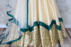 Splurge on this designer cream silk net embroidery lehenga with cream-coloured dupatta to look nothing less than a dream. Escalate your style appeal with the emerald-hued blouse embroidered to perfection and drape the dupatta. Shop beautifully handcrafted lehengas online or visit Pure Elegance store in USA. -lehenga skirt