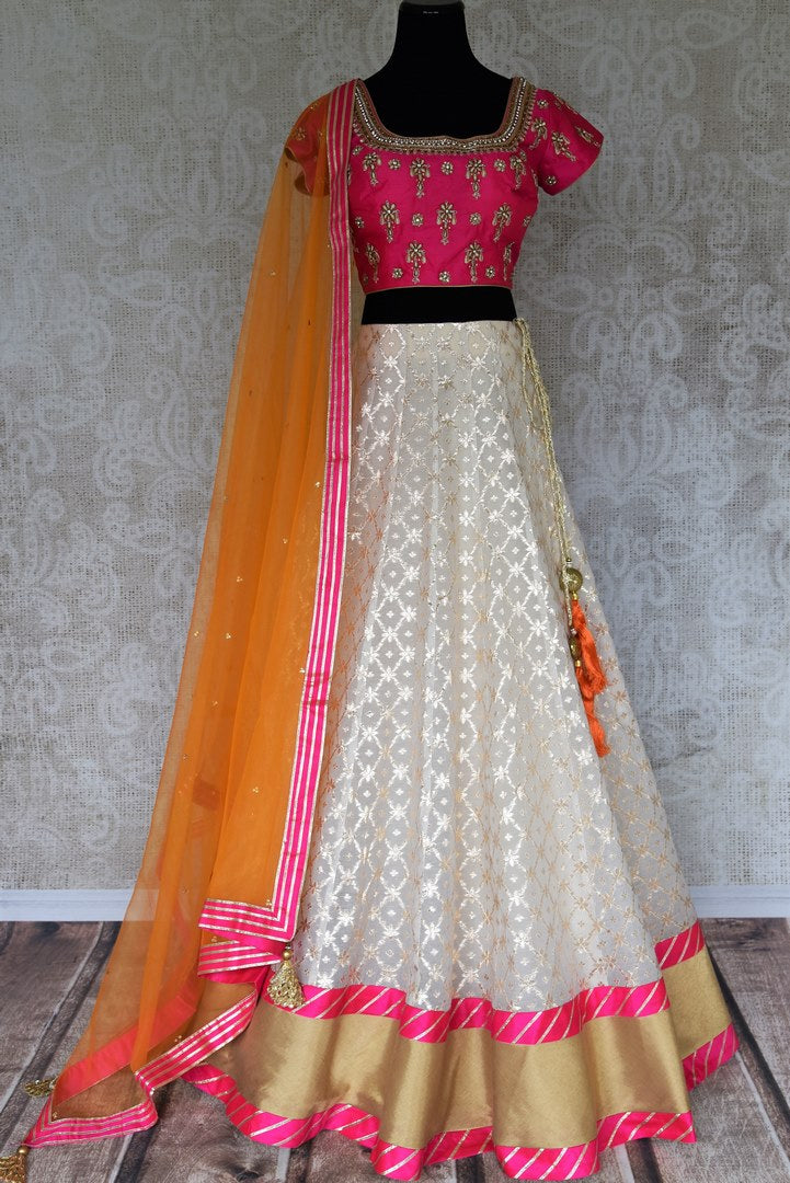 Leave them spellbound as you show up in this jaw-dropping white chanderi silk lehenga accompanied with a stunning hot pink zardosi embroidered blouse. Complete the look with the orange sequinned net dupatta with pink border. Shop Indian dress, lehenga choli, ikkat sari online or visit Pure Elegance store, USA.-full view