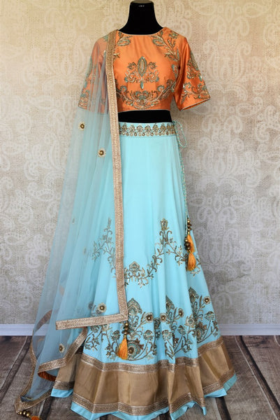 Doll up chic in this statement-worthy blue embroidery designer lehenga paired with contrasting orange embroidered designer blouse and buta work powder blue sheer net dupatta to add grace. Shop handcrafted designer dresses, indo-western dresses, lehengas online or visit Pure Elegance store in USA. -full view