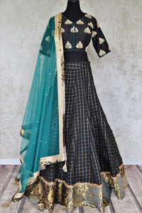 Heavily ornamented royal blue silk lehenga with checkered details and banarsi border comes with a gorgeous blue and beige silk embroidered blouse. Let the teal sequinned net dupatta fall immaculately for the feminine look. Shop designer sarees, lehenga cholis, Indian dresses online or visit Pure Elegance store, USA. -full view