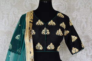 Heavily ornamented royal blue silk lehenga with checkered details and banarsi border comes with a gorgeous blue and beige silk embroidered blouse. Let the teal sequinned net dupatta fall immaculately for the feminine look. Shop designer sarees, lehenga cholis, Indian dresses online or visit Pure Elegance store, USA. -blouse front