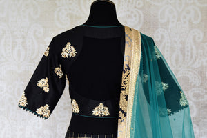 Heavily ornamented royal blue silk lehenga with checkered details and banarsi border comes with a gorgeous blue and beige silk embroidered blouse. Let the teal sequinned net dupatta fall immaculately for the feminine look. Shop designer sarees, lehenga cholis, Indian dresses online or visit Pure Elegance store, USA. -blouse back