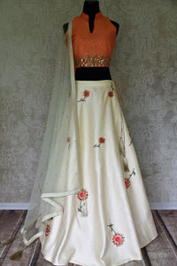 Grace the special events in this white silk lehenga with floral embroidery. Style it with a gorgeous peach embroidered halter neck blouse and drape a pretty sheer net white dupatta. The sequin work dupatta looks incredible. Shop silk sarees, wedding lehengas, bridal dresses online or visit Pure Elegance store, USA. -full view