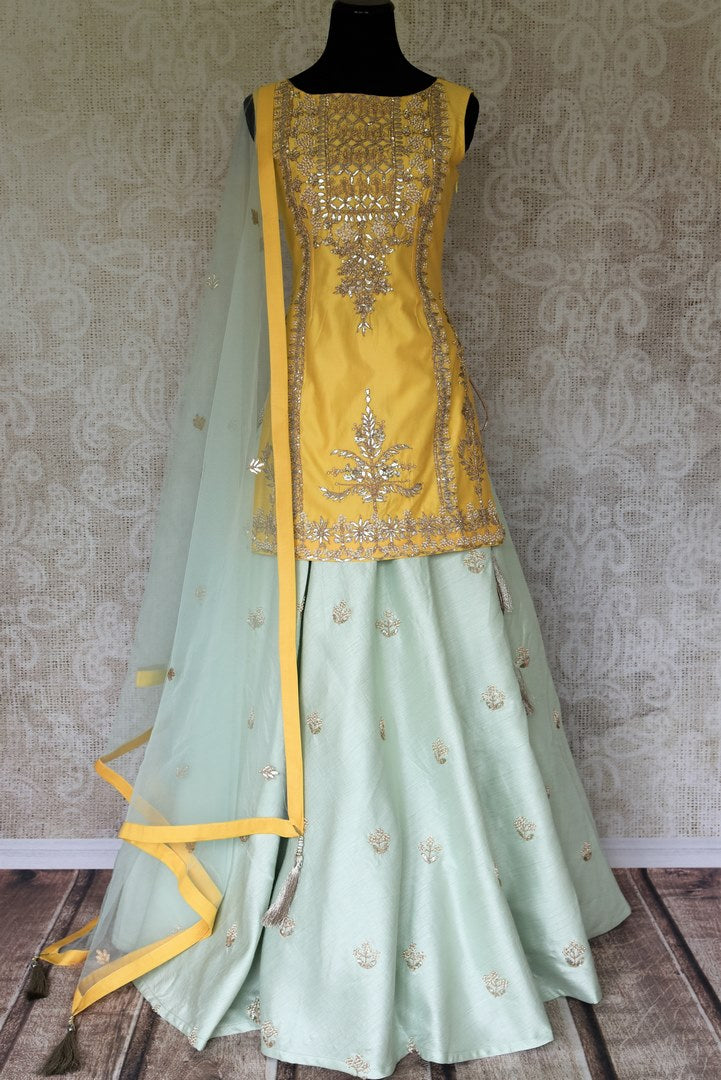 Wedding season calls for some serious indulgence and this mint green moti embroidery lehenga will not fail you. It comes with a bright yellow embroidered kurti. Drape the fancy mint green net dupatta on the side. Shop Indian dresses, anarkali suits, lehenga online or visit Pure Elegance store, USA. -full view
