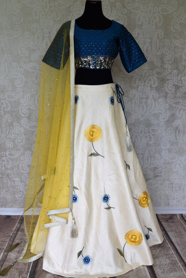 Be the kitchsy conversation-starter in this white floral embroidered raw silk lehenga. It comes with a royal blue silk blouse with intricate embroidery. Drape a yellow sequin work dupatta for an easy breezy chic look. Shop handcrafted lehenga choli, anarkali suits, saris online or visit Pure Elegance store, USA. -full view