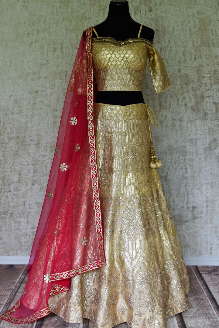 Sparkle in glory in our exclusively designed gold gota patti work lehenga with intricate embroidery. Style it with a stunning gold cold-shoulder embroidered blouse and drape a red sheer net embroidered dupatta. Shop handloom sarees, bridal salwar kameez, bridal lehengas online or visit Pure Elegance store, USA. -full view