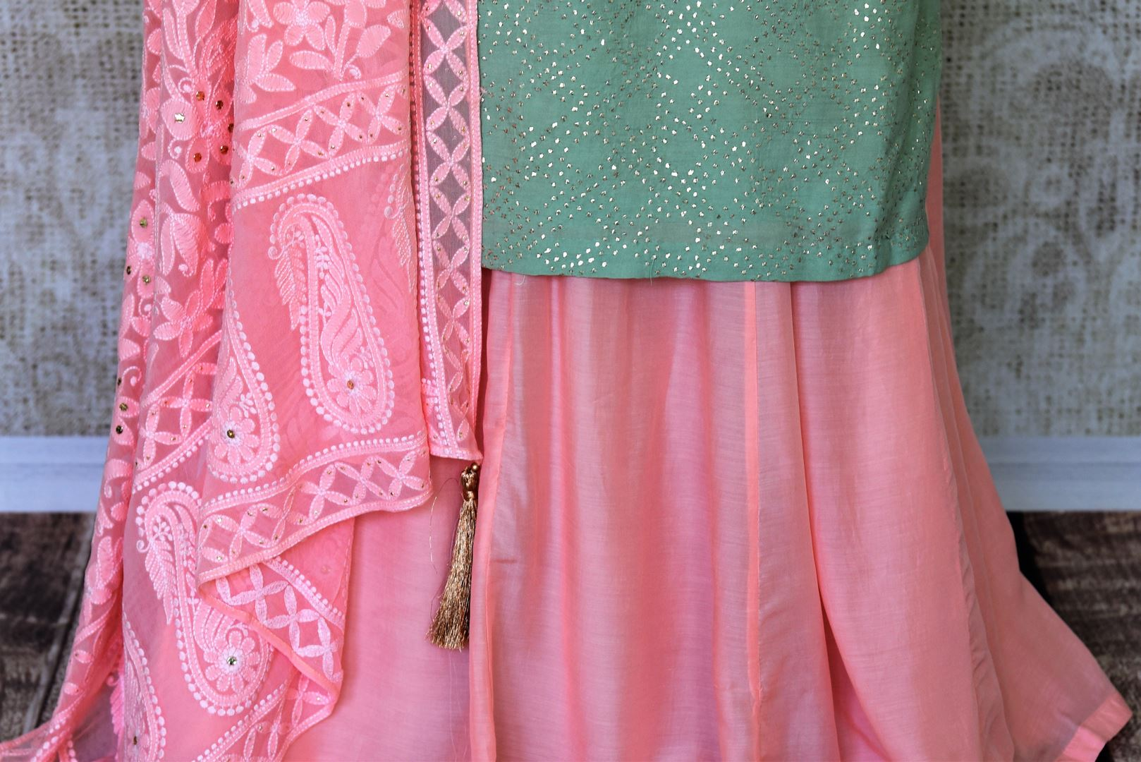 Ooze an oomph in this mint green chanderi silk sequin work long kurta. The beautifully handcrafted kurta is styled with contrasting pink flowy silk skirt. Drape the pleasing pink chikankari dupatta to complete the look. Shop designer suits, lehenga sets, Indian dresses online or visit Pure Elegance store,USA. -skirt