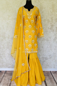 Unfold the summer sunshine with this bright yellow chanderi silk gota patti embroidered kurta and sharara pants. It's a perfect ensemble for day-time events when styled with a net yellow dupatta. Shop Indian dresses, anarkali suits, lehenga sets online or visit Pure Elegance store, USA.  -full view