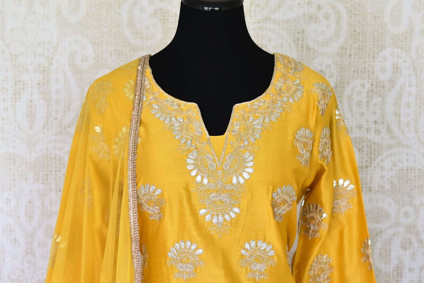 Unfold the summer sunshine with this bright yellow chanderi silk gota patti embroidered kurta and sharara pants. It's a perfect ensemble for day-time events when styled with a net yellow dupatta. Shop Indian dresses, anarkali suits, lehenga sets online or visit Pure Elegance store, USA.  -kurta front