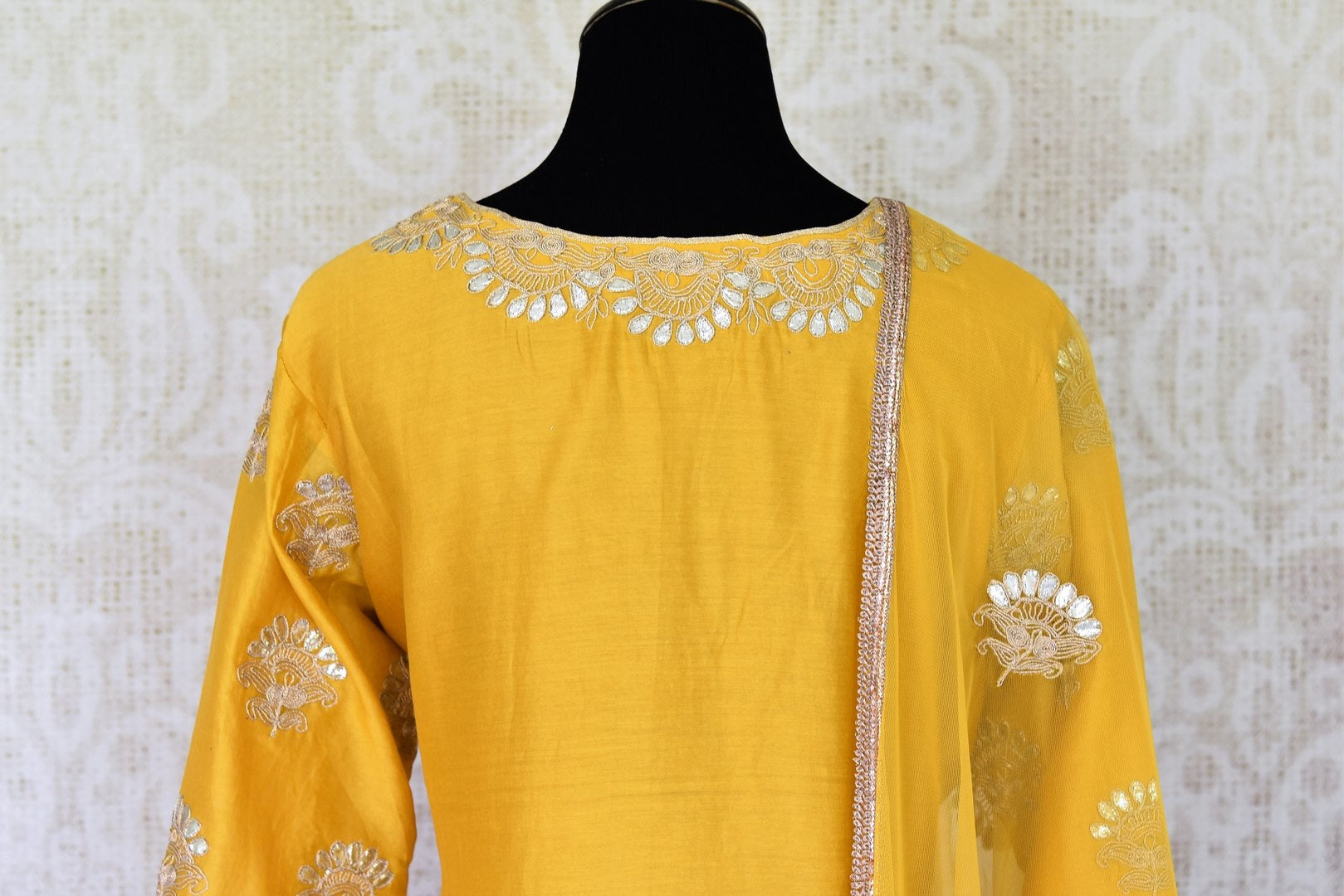 Unfold the summer sunshine with this bright yellow chanderi silk gota patti embroidered kurta and sharara pants. It's a perfect ensemble for day-time events when styled with a net yellow dupatta. Shop Indian dresses, anarkali suits, lehenga sets online or visit Pure Elegance store, USA.  -kurta back