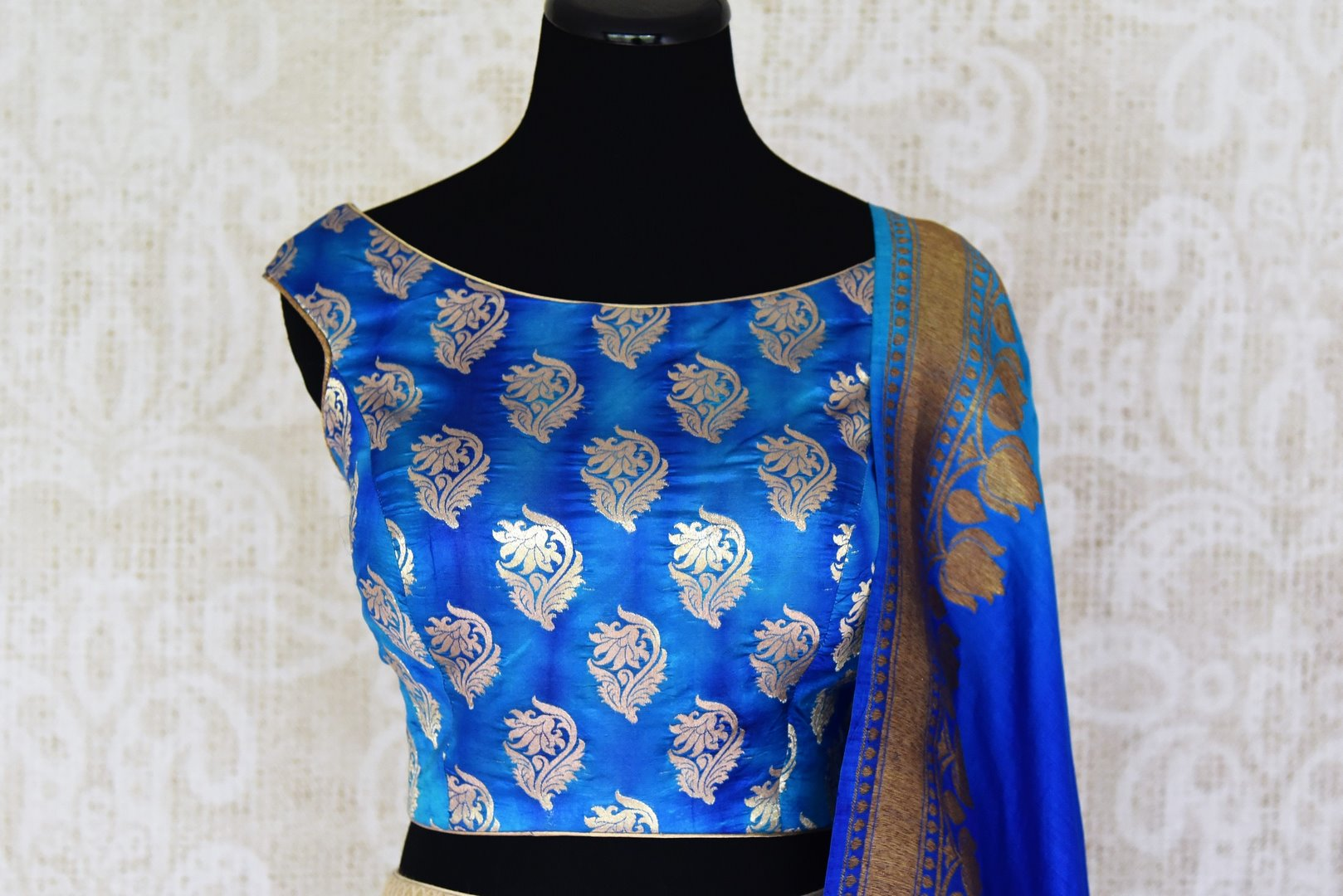 Buy gold Banarasi silk lehenga with blue sleeveless choli online in USA and dupatta. Find a range of stunning designer lehengas in USA at Pure Elegance Indian clothing store. Elevate your traditional style with a range of designer sarees, Indian clothing, and much more also available at our online store.-blouse front