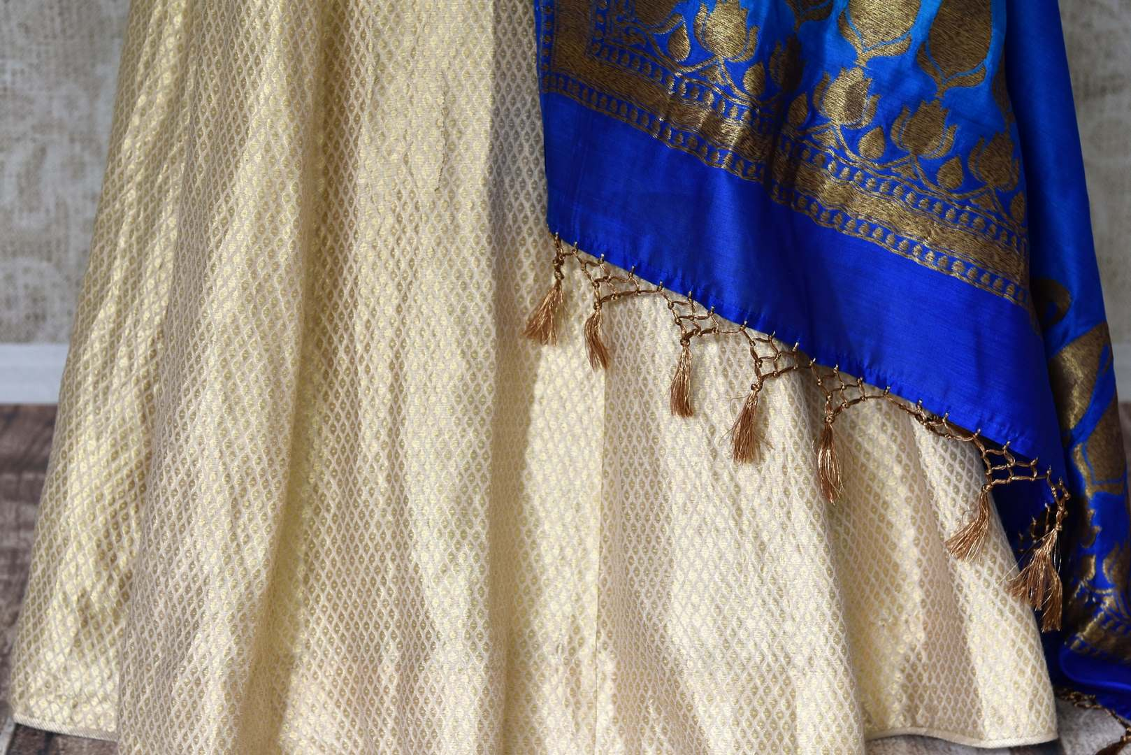 Buy gold Banarasi silk lehenga with blue sleeveless choli online in USA and dupatta. Find a range of stunning designer lehengas in USA at Pure Elegance Indian clothing store. Elevate your traditional style with a range of designer sarees, Indian clothing, and much more also available at our online store.-skirt