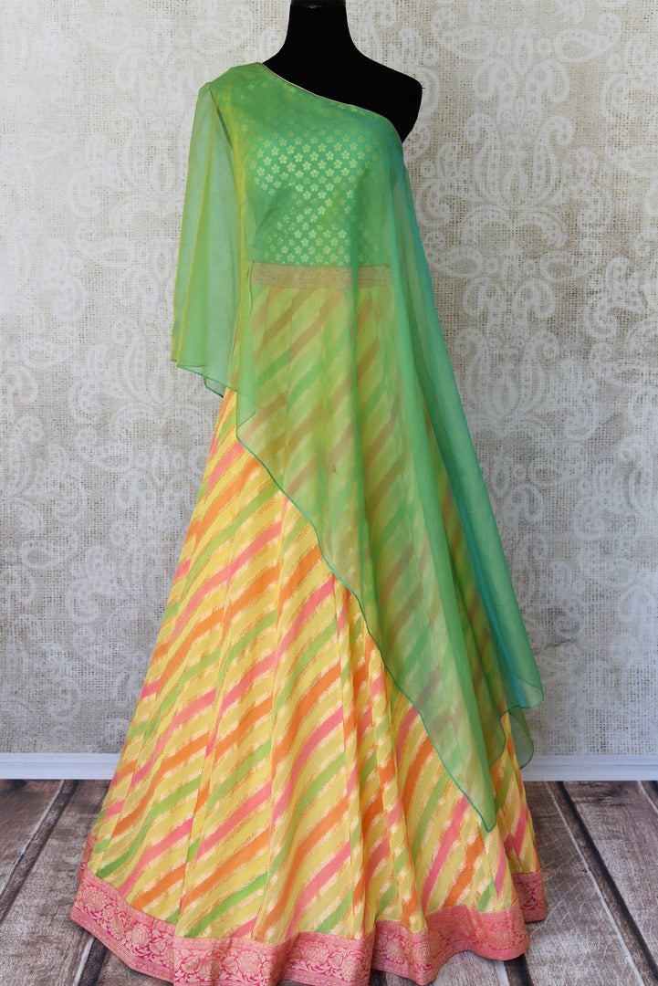 Shop green and yellow khaddi Banarasi skirt with one shoulder blouse online in USA. Adorn your style with a range of exquisite Kanchipuram silk saris from Pure Elegance clothing store in USA. We have an exquisite range of Indian designer sarees, silk sarees, Banarasi saris and many other varieties also available at our online store.-full view