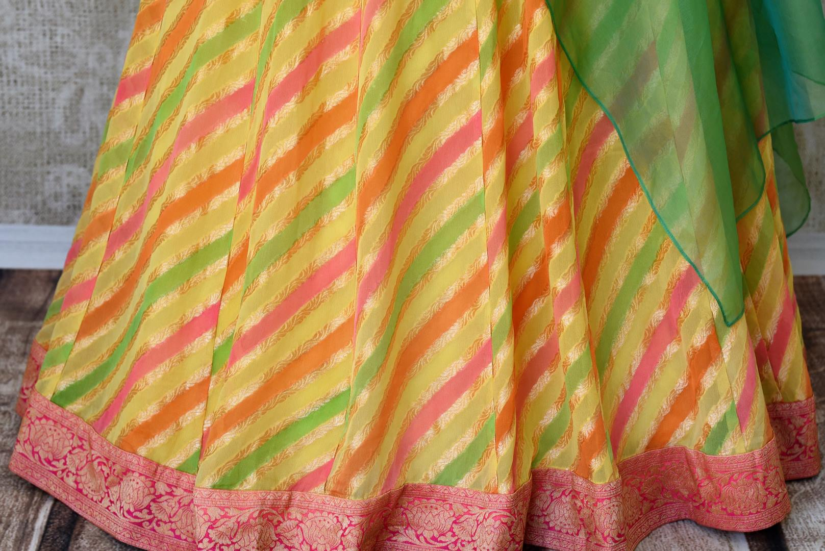 Shop green and yellow khaddi Banarasi skirt with one shoulder blouse online in USA. Adorn your style with a range of exquisite Kanchipuram silk saris from Pure Elegance clothing store in USA. We have an exquisite range of Indian designer sarees, silk sarees, Banarasi saris and many other varieties also available at our online store.-skirt