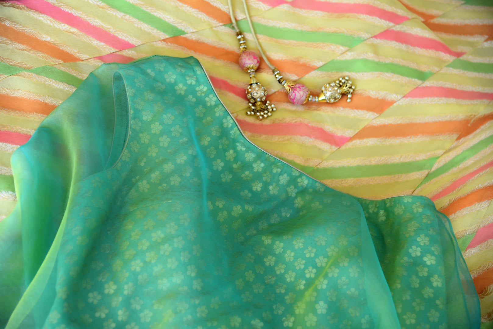 Shop green and yellow khaddi Banarasi skirt with one shoulder blouse online in USA. Adorn your style with a range of exquisite Kanchipuram silk saris from Pure Elegance clothing store in USA. We have an exquisite range of Indian designer sarees, silk sarees, Banarasi saris and many other varieties also available at our online store.-details