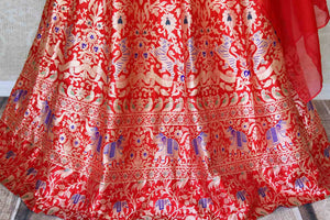 Buy red muga Banarasi lehenga online in USA with one shoulder choli. Make every occasion special by choosing the best of designer dresses from Pure Elegance Indian clothing store in USA, Shop from a range of stunning designer lehengas, wedding dresses, Indowestern dresses from our online store.-lehenga