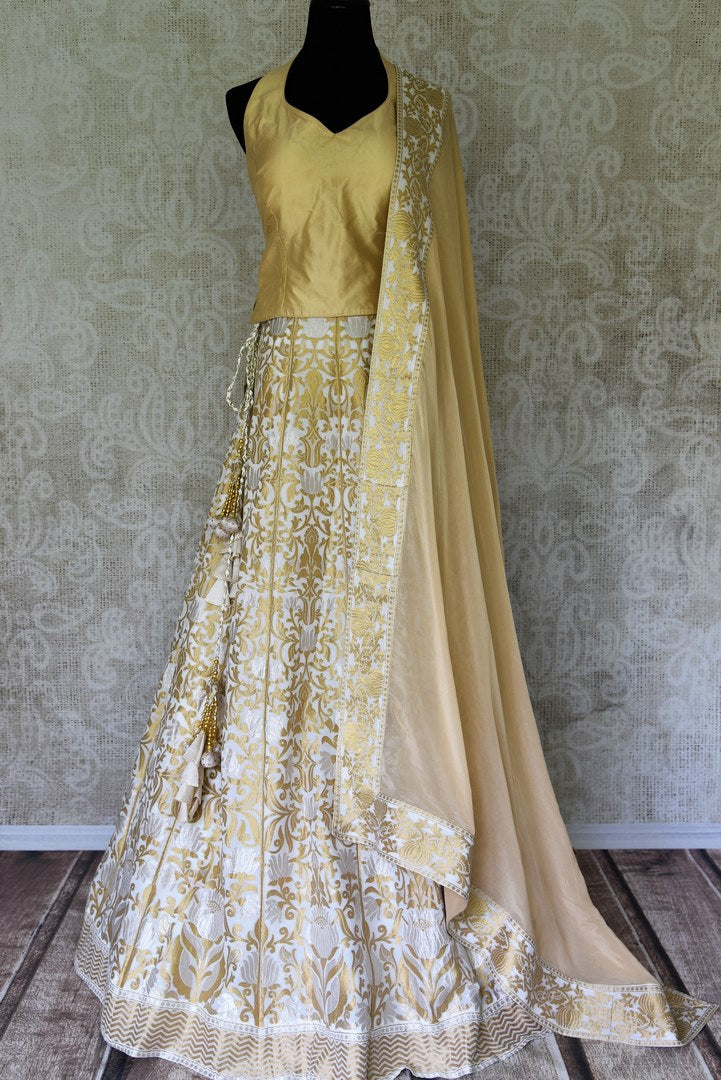 Buy off-white Banarasi lehenga online in USA with halter neck choli. Make every occasion special by choosing the best of designer dresses from Pure Elegance Indian clothing store in USA, Shop from a range of stunning designer lehengas, wedding dresses, Indowestern dresses from our online store.-full view