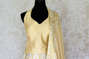 Buy off-white Banarasi lehenga online in USA with halter neck choli. Make every occasion special by choosing the best of designer dresses from Pure Elegance Indian clothing store in USA, Shop from a range of stunning designer lehengas, wedding dresses, Indowestern dresses from our online store.-blouse front