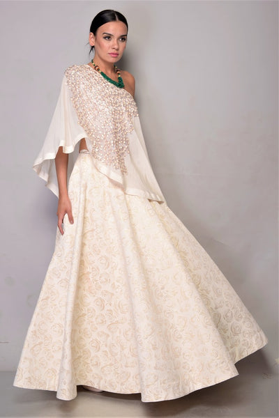 Shop Offwhite Skirt with Off Shoulder Cape online in USA. Bring glamor to your wedding look with elegant designer wedding gowns, wedding dresses available at Pure Elegance Indian clothing store for women in USA or shop online.-full view